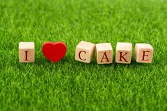 I love cake in wooden cube. With heart shape on grass Stock Photo