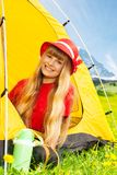 I love camping. Portrait of blond happy smiling little years old girl sitting in camping tent in yellow dandelion field royalty free stock image