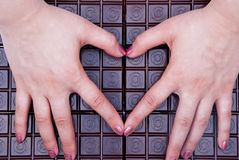 I love chocolate. Hands shaped in heart, bar of chocolate in background Stock Photos