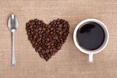 I love coffee. Heart shape made from coffee beans with a spoon and cup of coffee on hessian spelling I love coffee
