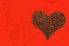 I love coffee. Heart made of coffee beans lying on the red background Stock Image