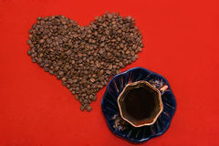 I love coffee. Heart made of coffee beans lying on the red background Stock Photography