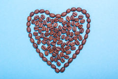 I love coffee. Coffee heart. Heart problems from coffee. Heart from coffee beans on a blue background royalty free stock photos