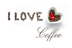 I love coffee - hearts, grains. I love written by coffee beans. The word coffee is written by handwriting. Bowl in the shape of a heart with coffee beans and two Stock Photos