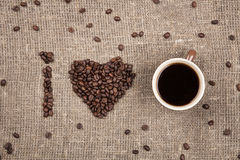 I love coffee made of coffee beans on burlap. Brown cup of coffee with coffe beans shaping heart Stock Image