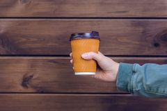 Free I Love Coffee! Person`s Hand Holding Cup Of Coffee In Front Of Brown Wooden Background Takeaway Takeaway Takeout Food Drink Beve Stock Images - 123581604