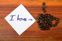 I love coffee on shortnote paper and coffee beans. Text i love coffee on shortnote paper and coffee beans on wooden background Royalty Free Stock Photo