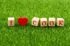 I love Cook in wooden cube. With heart shape on grass Stock Image