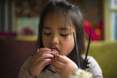 I love cupcake. One little girl eating a cupcake, seems really enjoying it Stock Images
