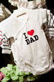 I love dad baby clothes. I love dad baby bodysuit clothes hanging up on display in shop royalty free stock image