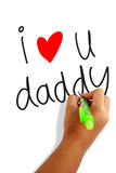 I love daddy. Girls hand holding a pen writing i love daddy greeting card Royalty Free Stock Images