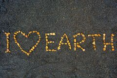 Free I Love Earth, Symbolic Message For Global Change And Protecting Environment. Tiny Stones Make A Writing On A Black Sand Background Royalty Free Stock Image - 171893256