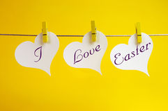 I Love Easter message hanging from pegs on a line. I Love Easter message written across 3 heart tags hanging from pegs on a line against a yellow background Stock Photos