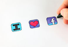 I love facebook. Tambov, Russian Federation - January 10, 2013 Womans hand with ballpoint pen draw signs - I, heart and facebook icon. Studio shot. Pictures Royalty Free Stock Image