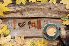I love fall still life. Cozy autumn still life: cup of coffee with warm woolen blanket and shaped candied peels, cinnamon and almonds among yellow leaves on royalty free stock images