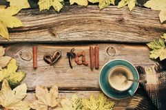 I love fall still life. Cozy autumn still life: cup of coffee with warm woolen blanket and shaped candied peels, cinnamon and almonds among yellow leaves on royalty free stock photography