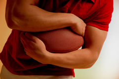 I love foot ball. Male in red shirt clutching football Stock Photography