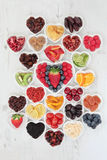 I Love Fruit. Fruit superfood background selection with fruits high in antioxidants, vitamin c and dietary fibre in heart shaped bowls over distressed white wood Stock Image