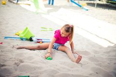 I love fun in the sand. Little happy girl playing in sand alone. Space for copy stock photos