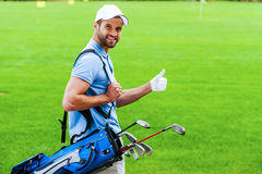I love golfing!. Rear view of young happy golfer carrying golf bag with drivers and looking over shoulder while standing on golf course Stock Image
