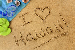 Hawaii beach summer vacation love. Hawaii beach writing : Hawaiian beach background with towel and flip flops and the words I Love Hawaii written in sand Royalty Free Stock Photography