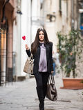 I love Italy. A young beautiful dark hair woman with a handbag walking with intent in the beautiful narrow streets of Genoa, an old Italian harbor city stock photos
