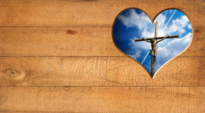 I Love Jesus - Crucifixion. Wooden wall with a hole in the shape of heart with Jesus crucified and blue sky with clouds Royalty Free Stock Images
