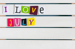 I Love July written with color magazine letter clippings on wooden board. Summer vacation concept, empty space for text.  Stock Images