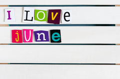 I Love June written with color magazine letter clippings on wooden board. Summer vacation concept, empty space for text. I Love June written with color magazine Royalty Free Stock Photos
