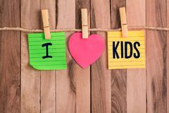 I love kids heart shaped note. I love kids text in color heart shaped note with clothespin and rope on wooden background stock photography