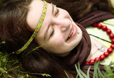 I love this life!. Hippie young woman lying on the green grass in good condition, focus on eye royalty free stock image