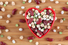 I love mixed legume beans. Mixed legume beans in a heart bowl. Close-up Royalty Free Stock Photography