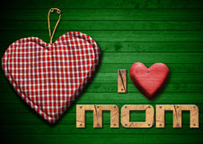 I Love Mom with Cloth Heart. I Love Mom written with wooden letters and red wooden hearts, handmade cloth heart hanging on green wooden background Royalty Free Stock Photography
