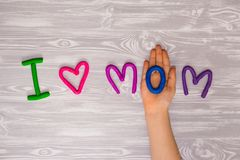 I love mom text from plasticine with kid hands on white wooden background. Happy mothers day. kids handmade craft present royalty free stock photography