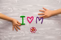 I love mom text from plasticine with kid hands on white wooden background. Happy mothers day. kids handmade craft present stock images