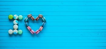 I love - multicolored macaroons in the form of hearts and confessions of lovers lie on a blue wooden background. Horizontally, copy space Royalty Free Stock Image