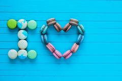 I love - multicolored macaroons in the form of hearts and confessions of lovers lie on a turquoise wooden background. Copy space Royalty Free Stock Images