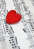 I love music. Red heart shaped glass over a music sheet Stock Photo
