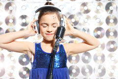 I love music. Child, teen, girl, singing into a microphone, a small singer Stock Photography