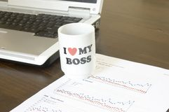 I love my boss. Coffee cup with laptop computer and business chart Stock Photos