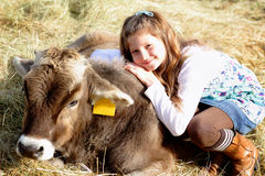 I love my cow. A pretty young farm girl with long blond hair, loving her cow. Shallow depth of field Royalty Free Stock Photography