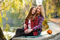 Blonde woman hugging her pretty daughter both smiling royalty free stock images