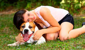 I love my dog. Beautiful girl laying on her dog (American Staffordshire Terrier) on a meadow in a park Royalty Free Stock Image