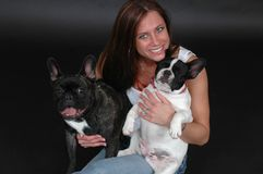 I Love my Dogs. Beautiful woman in blue jeans sitting on the floor against a black drop. Woman with her French Bull dogs Royalty Free Stock Images