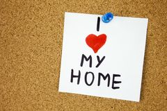 I love my home sticky note on a home on cork board background Royalty Free Stock Photography