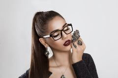 I love my jewelry. Woman tan girl in eye glasses holding brooch stock photo
