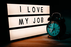 I love my job. Business and occupation motivational message on lighbox in the office next to the vintage style clock stock images