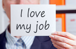 I love my job - businesswoman in the office. I love my job - businesswoman holding card with text in the office stock photo