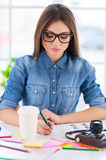 I love my job!. Cheerful young businesswoman in casual wear writing something in note pad while sitting at his working place Royalty Free Stock Photo
