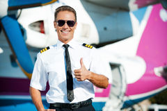 I love my job!. Confident male pilot in uniform showing his thumb up and smiling while standing in front of the airplane Stock Photos